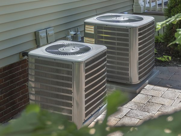 Two air conditioning units sitting outside.
