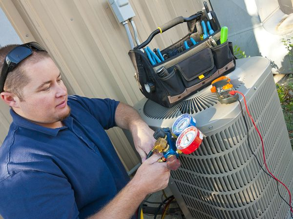 Air conditioner repair man checking levels on an air conditioning unit.