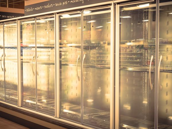 Empty commercial fridges at grocery store.