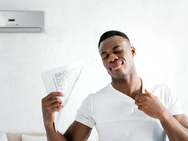 African American man hot inside of his home; fanning a newspaper in front of AC.
