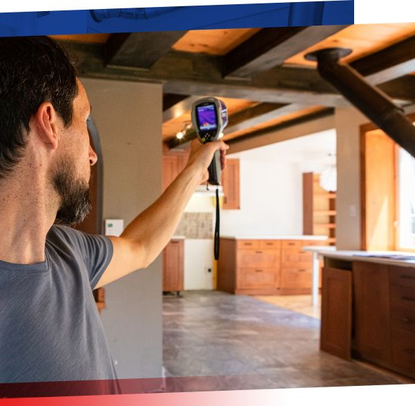 Image of man measuring thermal temperatures in house