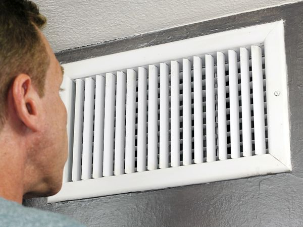 Male examines an indoor air duct.