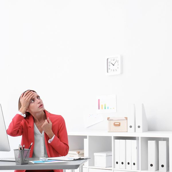 Young woman suffering from heat under broken air conditioner in office.