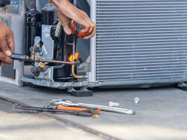 Air conditioning repair technician using a welder to fix a unit.