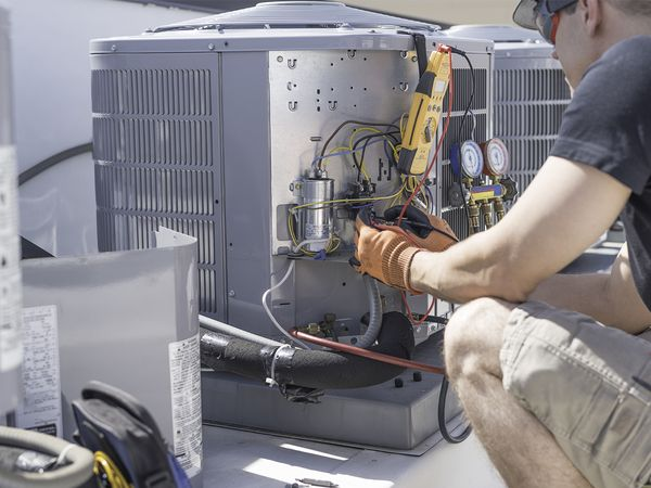 Hvac repair technician using a voltmeter to test components on an air conditioner condenser.