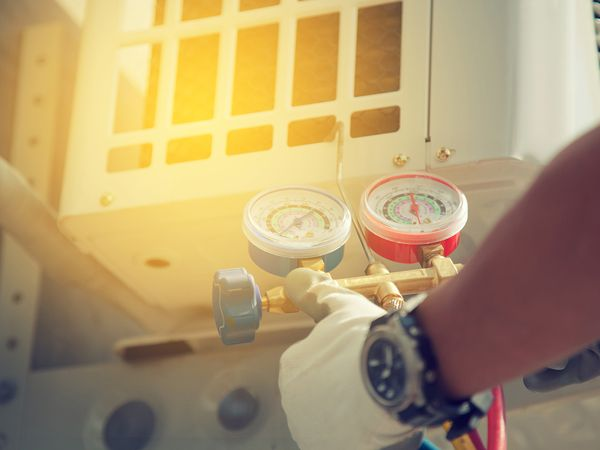 Air Conditioning Technician with manometers measuring equipment for filling air conditioners.
