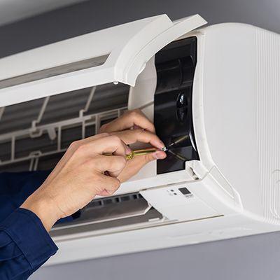 HVAC technician tightening the screw on an HVAC unit.