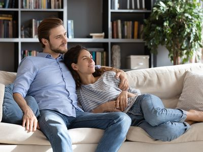 Happy young couple relaxing on cozy sofa at home.