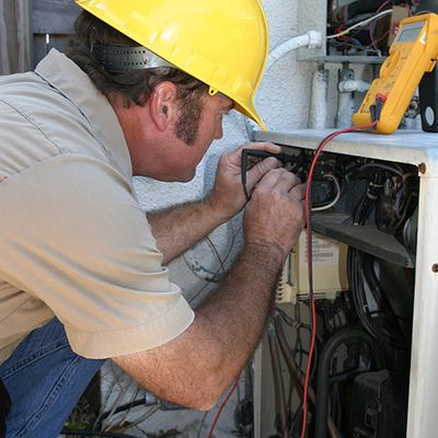 HVAC technician using tools to inspect a unit.