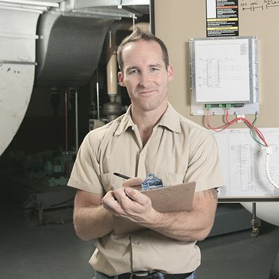 HVAC technician standing while holding a clipboard.