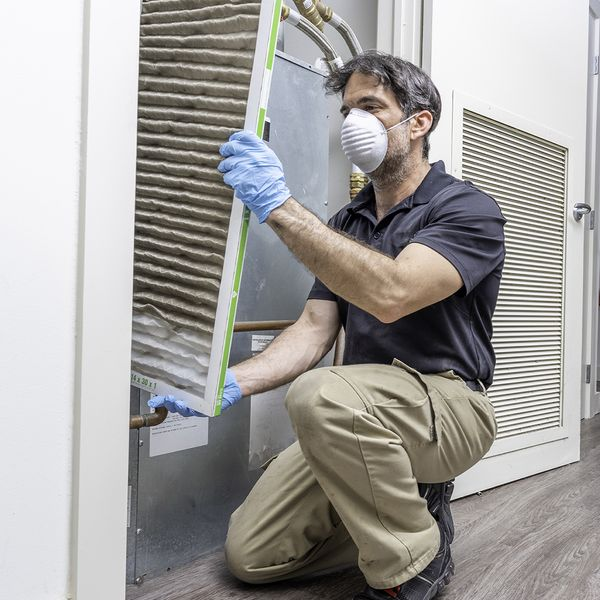 Male HVAC technician removes a dirty air filter in an office building.