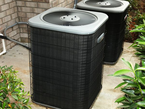 Central air conditioner units on cement slab outside.