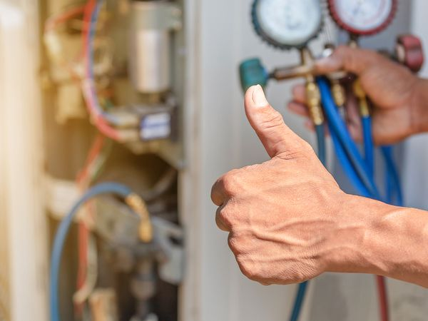 Air conditioning repair technician giving a thumbs up after fixing a unit.