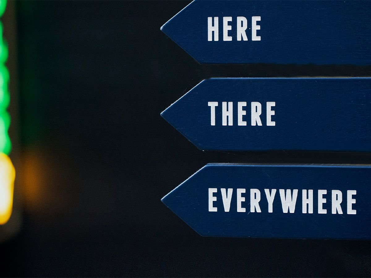 """Three layered signs that read,  """"Here, There, Everywhere."""""""