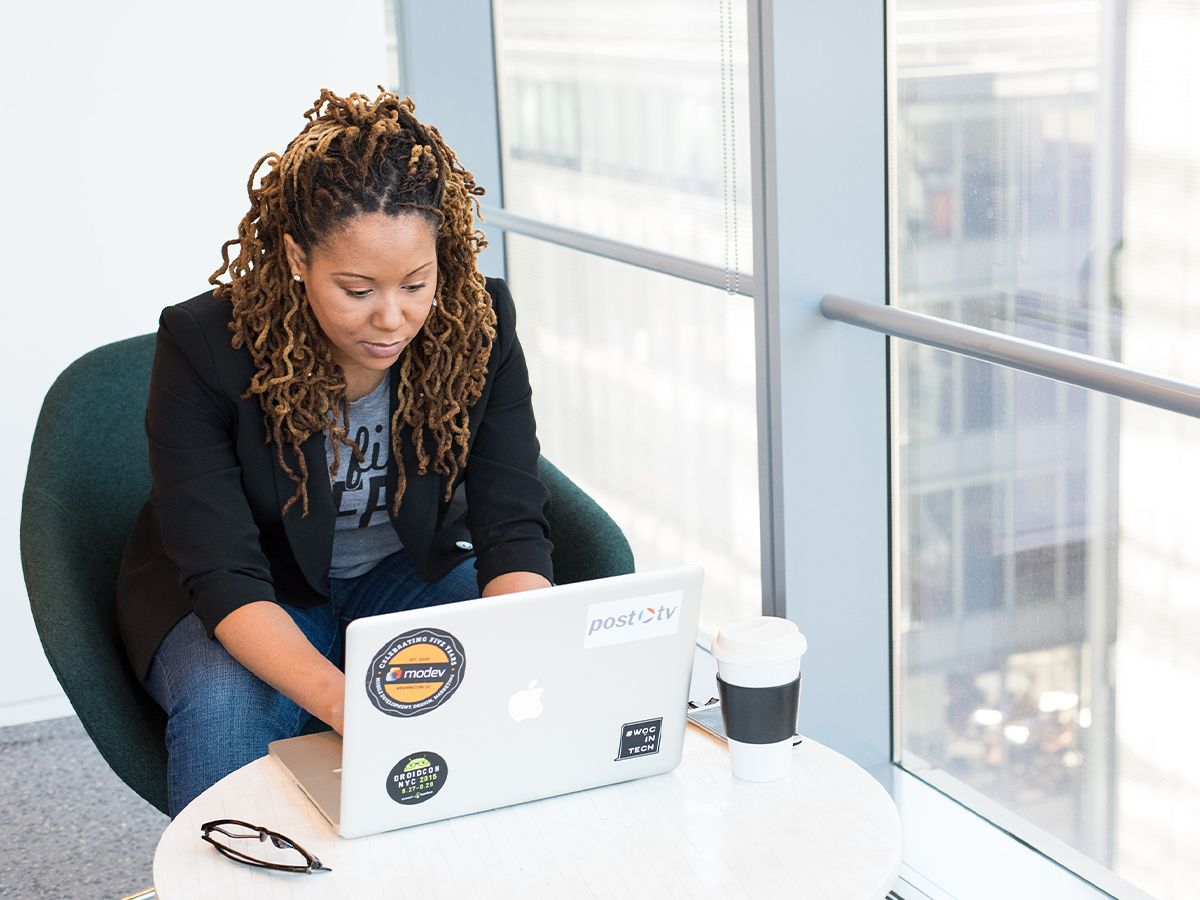 A Black woman working at a laptop.