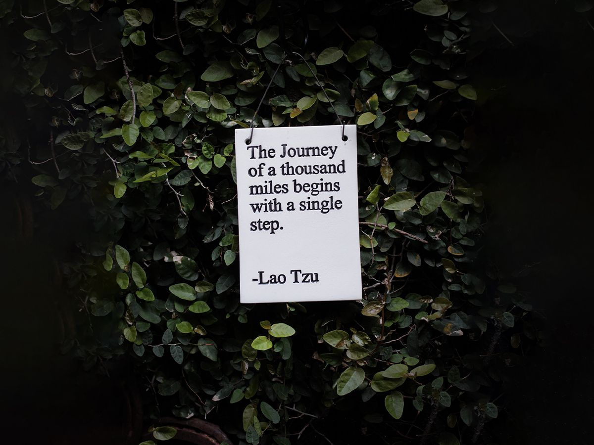 """A sign that reads, """"The journey of a thousand miles begins with a single step. -Lao Tza"""""""