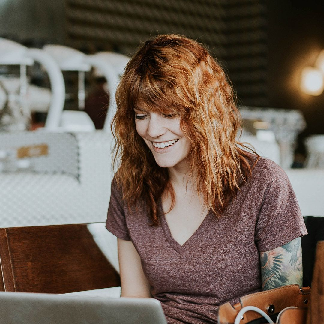 A smiling woman sitting at her laptop