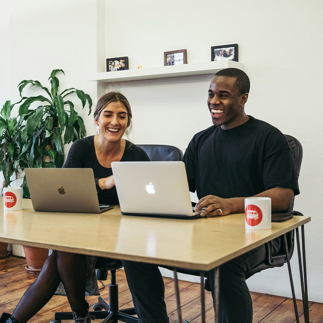 Two happy young professionals sitting in front of laptop computers.