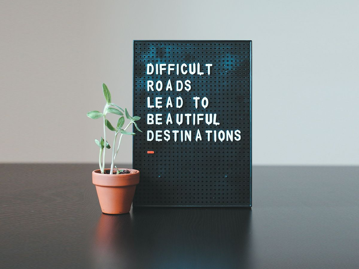 """A board that reads,  """"Difficult roads lead to beautiful destinations."""""""