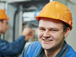 Electrician smiling at camera while electrician in background works on panel box
