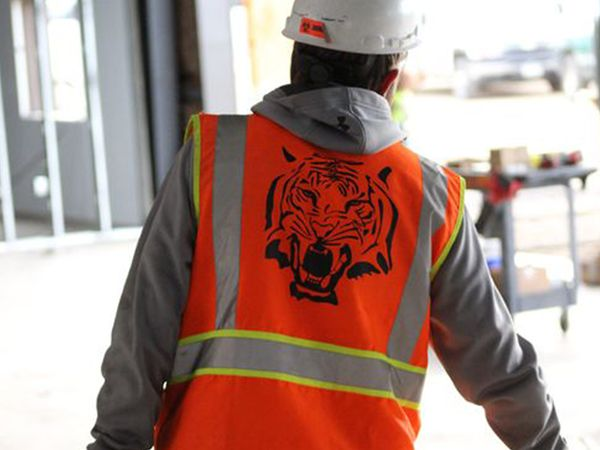 electrician in a safety vest with Tiger logo walking away from the camera