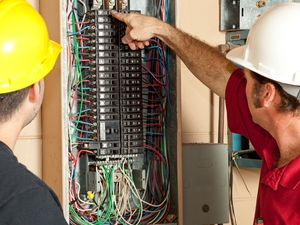 Lead electrician showing apprentice electrician various wire connections