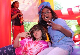 2 girls give the peace sign and laugh in a bouncy castle on a sunny day