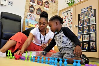 female child care educatorand small boy play with colourful toys