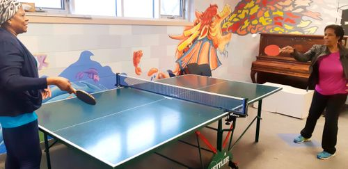 two senior ladies play ping pong inside recreation room