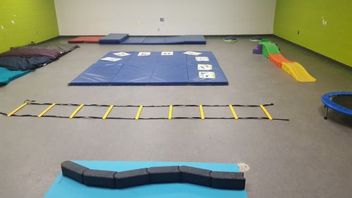 gym mats, trampoline, and children slide laid out inside safe gym area for small children