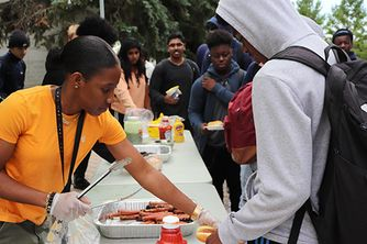 Youth outreach worker serves hotdogs to teenage boy. A line of teenagers stand behind ready to receive a hotdog also.
