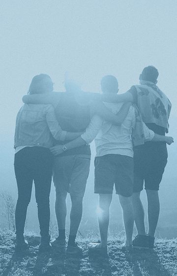 Group of people holding each other facing the sunrise