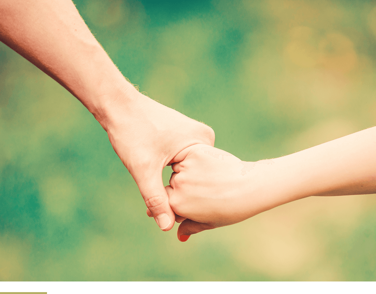 father holds his child's hand.