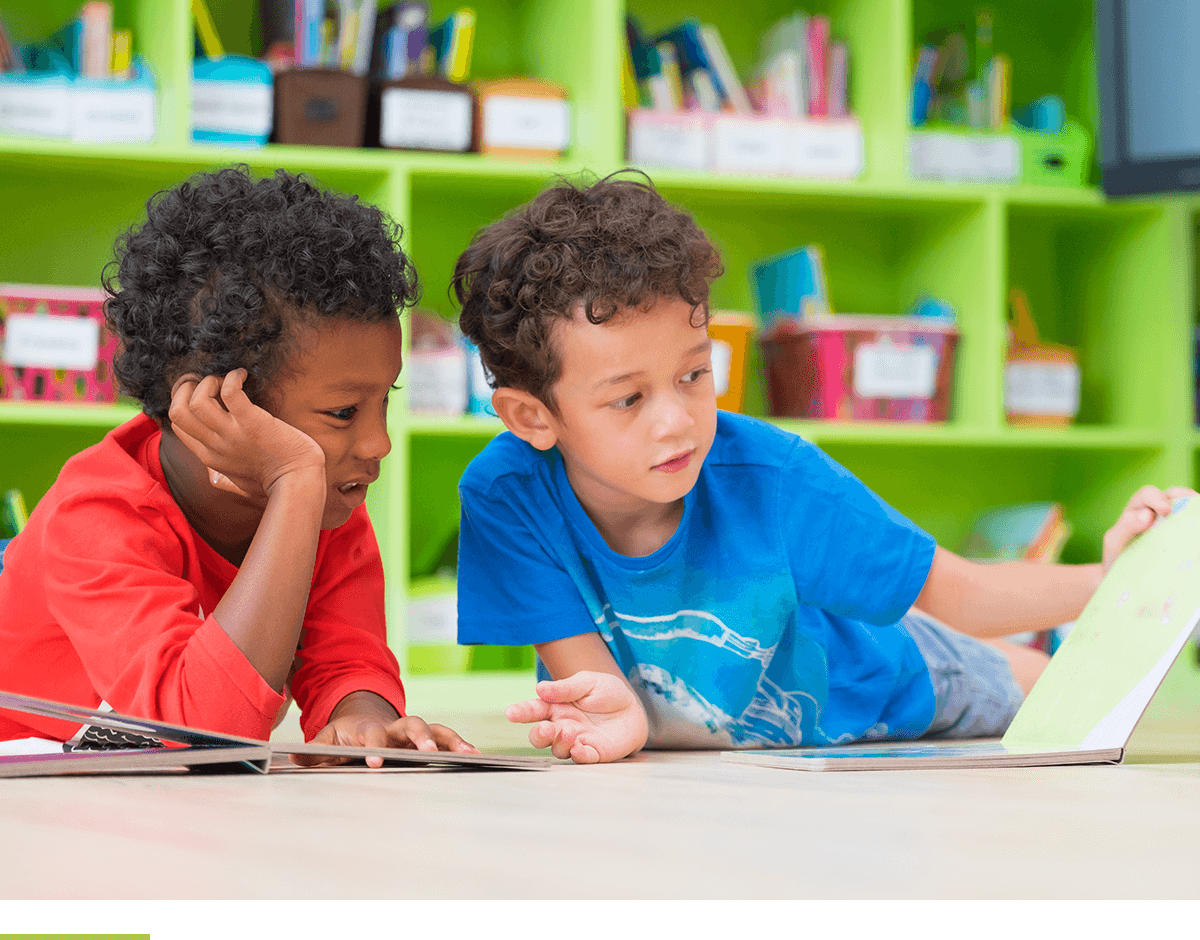 Two boy kids lay down on floor and reading a book in preschool library