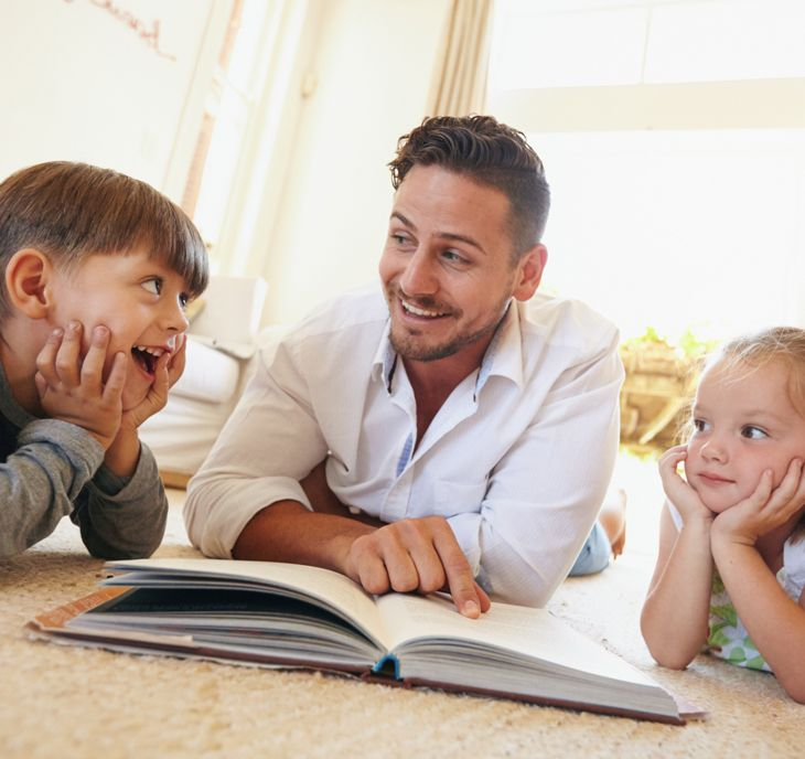 father reading with his son and daughter