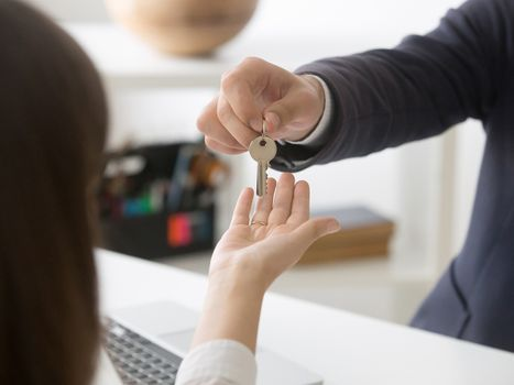 Man handing over a house key to a new homeowner.