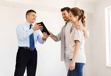 Image of a real estate agent inside a home with potential buyers