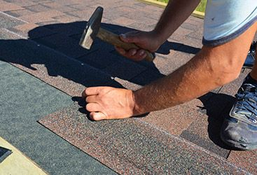 Image of a roofing contractor installing shingles.
