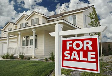Image of a house with a for sale sign out front.