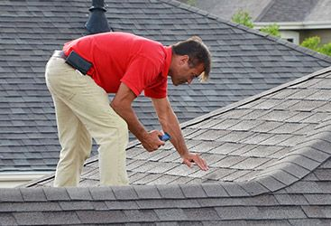 Image of a roof inspector looking closely at a roof.